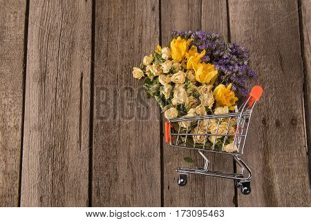 Spring floral composition with Beautiful various flowers in small shopping trolley on wooden table