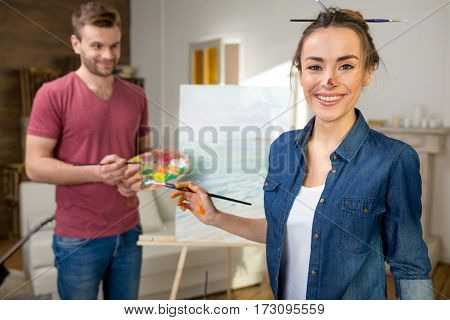 Happy young couple of artists painting together at home