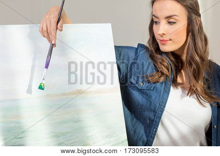 Beautiful young woman artist with paintbrush leaning at easel with picture