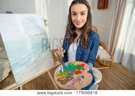 Attractive young woman artist with paintbrush and palette smiling at camera