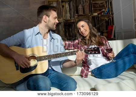 Smiling young woman holding wine glass and looking at handsome man playing guitar