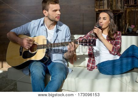 Young woman drinking wine and looking at handsome man playing guitar