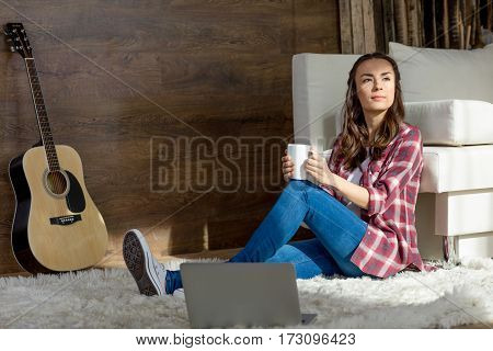 Thoughtful young woman sitting on carpet with tea cup and looking away