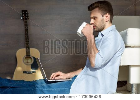 Handsome young man drinking tea and using laptop at home