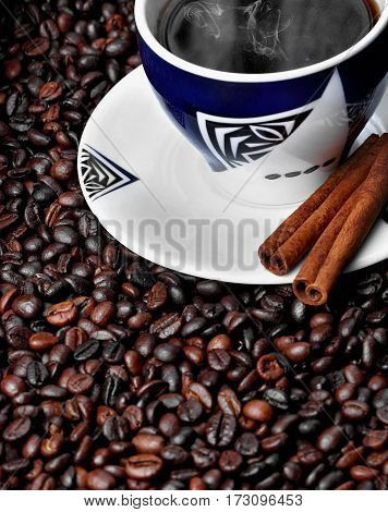 Cup with hot coffee and cinamon sticks on texture coffe beans.Plate with african ornament.Copy space.top view