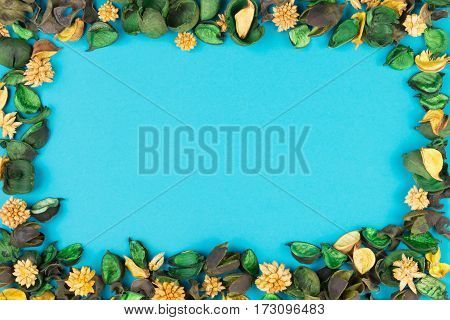 Dried flowers and leaves composition as frame on blue background. Top view, flat lay