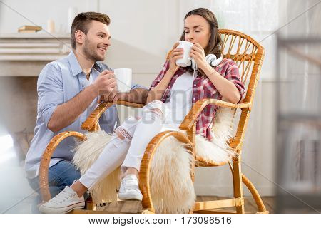 Happy young man with cup looking at woman drinking tea in rocking chair