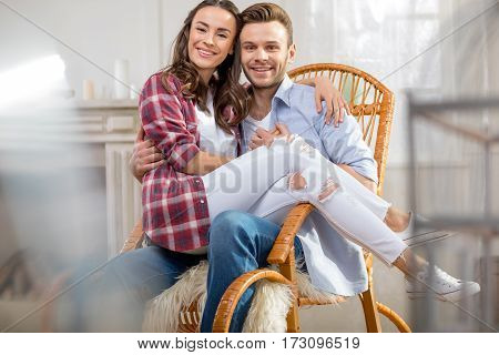 Happy young couple sitting in rocking chair and smiling at camera