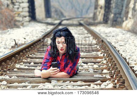 Teenage girl lying on the railway and writes a message on mobile