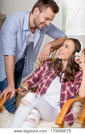 cheerful woman in headphones and smartphone in hands looking at man near by
