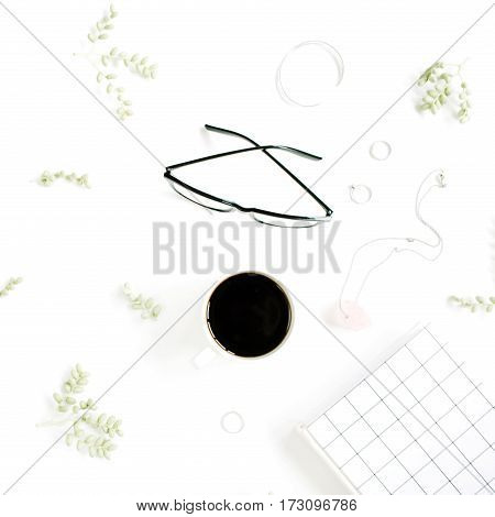 Coffee cup notebook glasses green branches and female accessories on white background. Flat lay top view