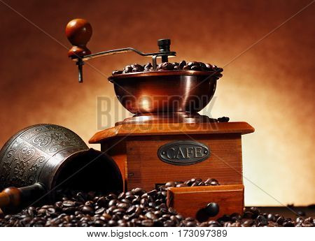still life with coffee beans and old coffee mill and turk on the wooden background.