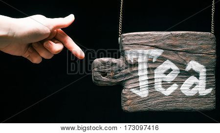 Vintage hanging wood sign with text 'Tea'. Hand pointing to the sign. Isolated over black background
