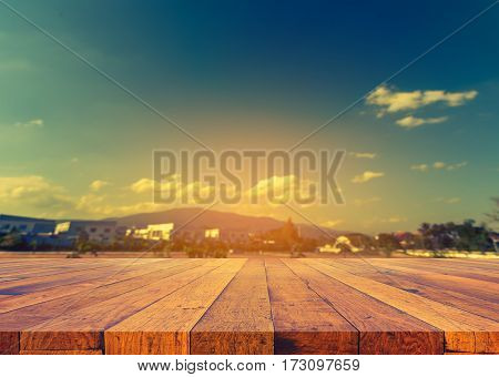 image of wood table and blur house and cloudy blue sky for background usage