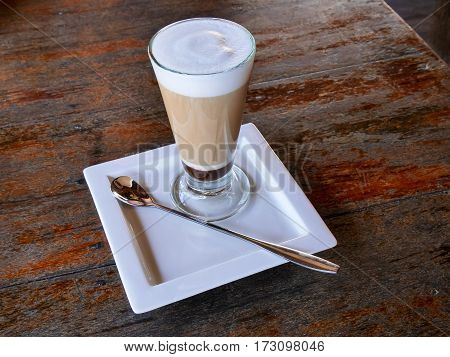 Latte macchiato in a beautiful glass a spoon and a white plate on a dark wooden table