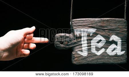 Retro hanging wood sign with text 'Tea'. Finger pointing to the sign. Isolated over black background
