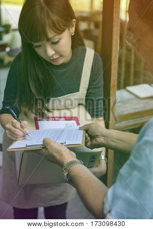 Young woman receive a parcel and sign the document