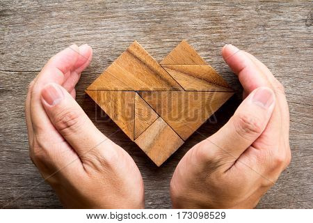 Hand cover tangram puzzle in heart shape on wooden background