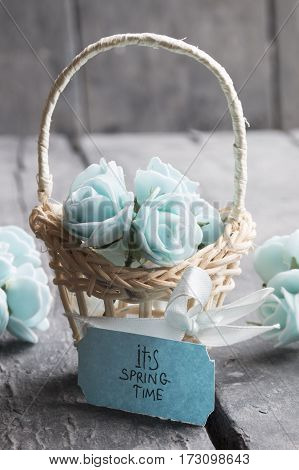 Bouquet of spring flowers in basket. Its spring Time tag.