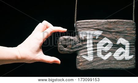 Old-fashioned hanging wood sign of cutting board with text 'Tea'. Hand touching the sign. Isolated over black background