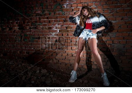Very Cute Sexy Young Female With Long Curly Hair And Fashion Make-up In Jeans Shorts And Red T-shirt