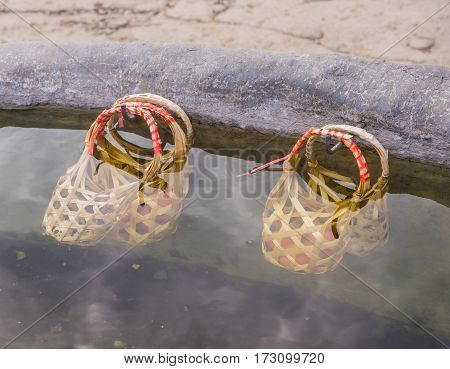 image of egg in bamboo basket boil in hot water at sankampaeng hot spring Chiang Mai Thailand.