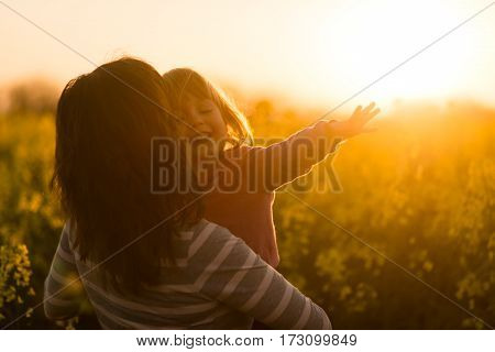 Mother and daughter spending leisure time in the meadow during sunset