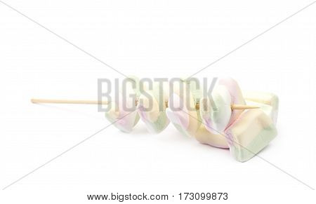 Multiple marshmallow candies on a wooden grill stick isolated over the white background