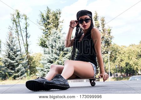 Stylish Girl In Sexy Shorts With A Skateboard Outdoors