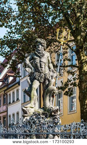 The bronze statue of Neptune with his trident in a classical pose in an urban square, Bamberg, Bavaria, Germany with historic townhouses in the background
