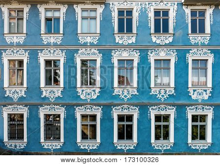 Straight on view of historic German building with blue facade and ornate windows painted white