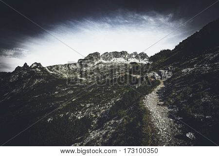 Scenic landscape view of a deserted trekking trail through rugged alpine scenery leading away across a steep slope towards distant peaks
