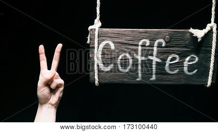Retro wood sign with text 'Coffee' hanging on ropes. Hand gesturing V for victory. Isolated over black background
