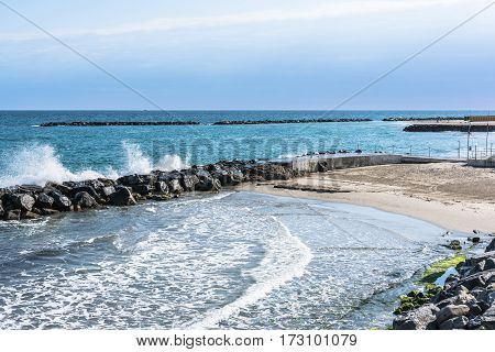 Sand beach and breakwater along the coast of Sanremo, Italy
