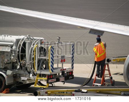 Man Refueling Commercial Jet Airplane Before Takeoff