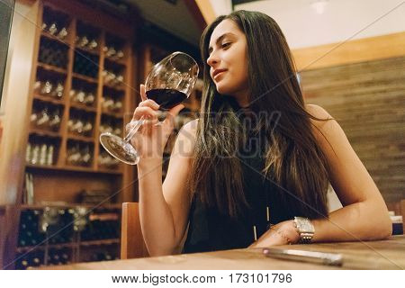 beautiful young girl enjoying delicious wine in a restaurant