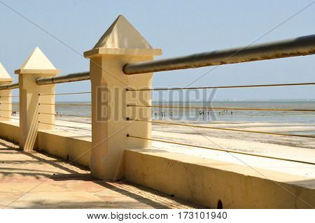 Barrier with concrete pylons a metal bar and steel cables separate the terrace and the beach