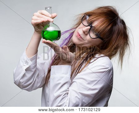 Scientist woman with green liquid on gray background
