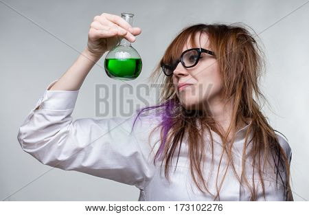 Scientist shaggy woman with green liquid on gray background