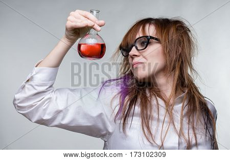 Scientist shaggy woman with red liquid on gray background