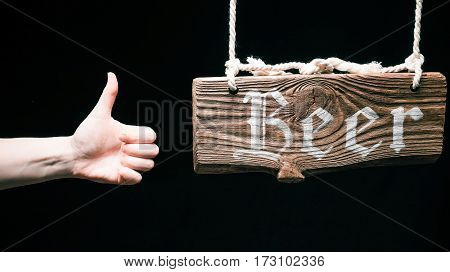 Retro hanging wood sign with text 'Beer'. Hand gesturing thumb up. Isolated over black background