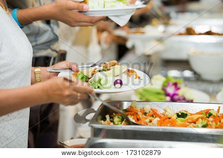 people group catering buffet food indoor in luxury restaurant with meat colorful fruits and vegetables