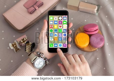 female hands jewelry holding phone with home screen icons apps