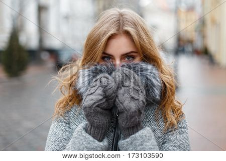 Beautiful Young Girl In Knitted Mittens Hides His Face And Warmed