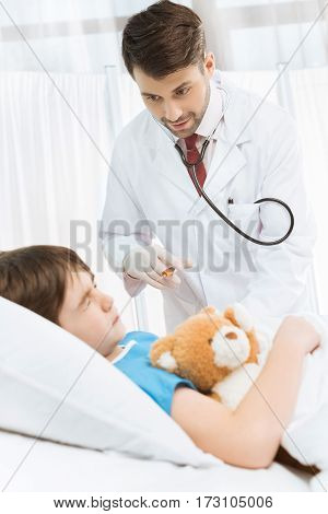 Scared little boy with teddy bear lying in hospital bed while doctor making injection