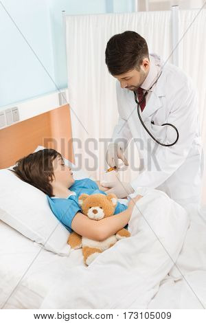 Little boy with teddy bear lying in hospital bed while doctor making injection