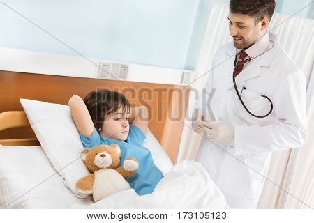 Smiling pediatrician looking at little boy lying with teddy bear in hospital bed