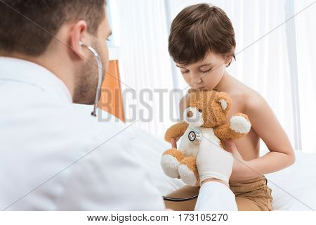 Man doctor with stethoscope examining little boy holding teddy bear