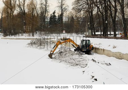 Moscow, Russia - January 17, 2017: Work on the excavator digs snow in winter in a park