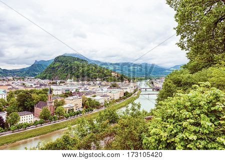 Panoramic view over stadt salzburg with salzach river, rainy day, bridge and mountains, austria